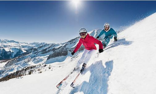 deux personnes qui descendent une piste de ski