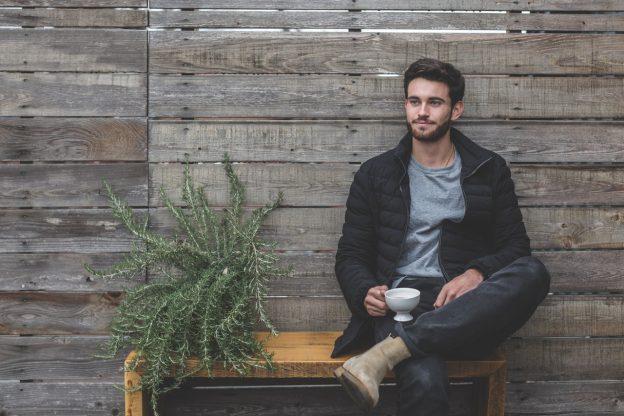 jeune homme assis sur un banc à côé d'une plante tenant une tasse